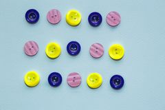 Collection of various multicolored sewing button on blue background. Yellow, purple, dark blue buttons. Sewing. Collection of various multicolored sewing button stock images