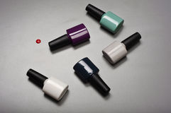 Collection of various nail polish bottles. On a gray background closeup royalty free stock image