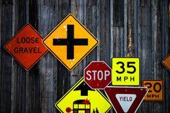 Collection of various road signs on rustic wooden wall. Old traffic signs on a barn wall royalty free stock image