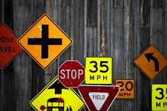 Collection of various road signs on rustic wooden wall Royalty Free Stock Images