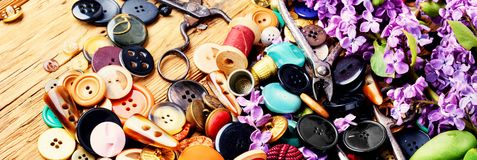Bright buttons and lilac branch. Collection of various sewing button,threads and scissors.Sewing accessories Stock Photos