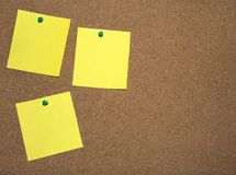 Three yellow notes papers are pinned on cork board for writing and a place for text. stock photos