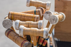 Collection of various vintage croquet mallets. Closeup of old painted wood croquet set outside on sunny day Stock Photos