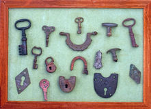 A collection of very old keys and locks in a wooden frame Royalty Free Stock Photography