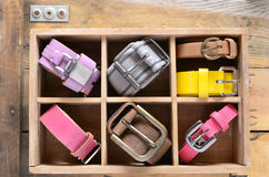 Collection of vintage belts in wooden crate Royalty Free Stock Images