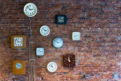 Collection of vintage, vintage clocks hanging on an old brick wall stock photos