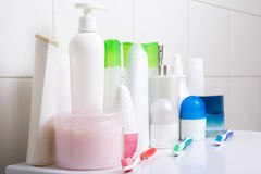 Collection of white cosmetic bottles over tiled wall Stock Photo