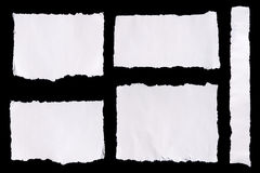 Collection of white ripped pieces of paper on black background Stock Photos