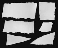 Collection of white ripped pieces of paper on black background Royalty Free Stock Photography