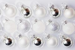 Collection of white and silver christmas balls in a box.  royalty free stock image