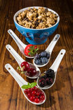 Collection of wild berries on white spoons and a cup of cereals Royalty Free Stock Photo