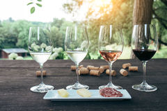 Collection of wine glasses on wooden table. During sunset stock photo