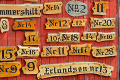 Collection of the wooden house numbers against the red painted wall. Stock Photography