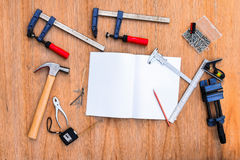 Collection of worktools, set of working tools. (Steel wrench, hammer, nails, bolts, wrenches, etc.) with notebook on the wooden ta Stock Image