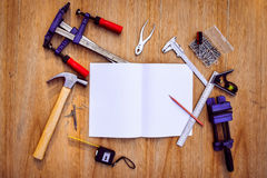 Collection of worktools, set of working tools. (Steel wrench, hammer, nails, bolts, wrenches, etc.) with notebook on the wooden ta Stock Images