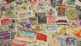 Collection of Worldwide Postage Stamps. Panning over a collection of worldwide postage stamps - Philately stock video footage