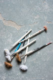 Collection of Worn Paintbrushes. An assortment of used paintbrushes with plaster-coated handles and split bristles on stone surface stock photo