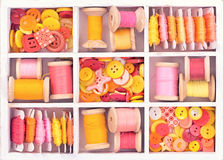 Collection of yellow, red, pink spools  threads  arranged in a white wooden box Stock Image