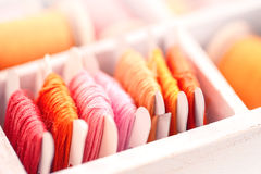 Collection of yellow, red, pink  threads  arranged in a white wooden box Royalty Free Stock Photo