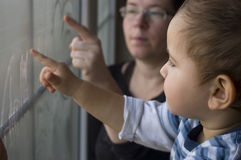 Collective creativity. Mom and two years old son paint on window Royalty Free Stock Images