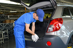 The collector fixes an internal upholstery of a luggage carrier. Of the car. Assembly shop of automobile plant Royalty Free Stock Photo