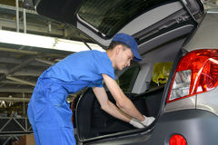 The collector fixes an internal upholstery of a luggage carrier. Of the car. Assembly shop of automobile plant Royalty Free Stock Photography