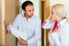 Collector getting the arrears from woman. Businessman trying to collect arrearages from women at home door Stock Image
