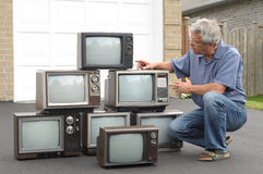 Collector of old TV sets. Senior, with his collection of old TV sets Royalty Free Stock Photo
