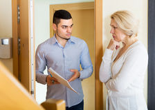 Collector to get the arrears. Collector is trying to get the arrears from mature unhappy women at home door Stock Photo