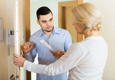 Collector to get the arrears. Young collector is trying to get the arrears from mature women at home door Royalty Free Stock Photo
