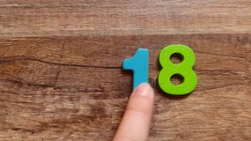 Collects from the colored wooden figures the number 2018 on the of the wooden table stock footage