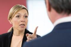 Collega aggressivo di Shouting At Male della donna di affari fotografia stock