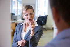 Collega aggressivo di Shouting At Male della donna di affari fotografie stock
