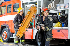Collega attento di Holding Hose While del pompiere immagini stock