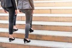 Collega delle donne di affari che cammina verso l'alto sulla scala fotografia stock