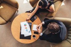 Collega di affari che si siede alla tavola con i grafici Fotografia Stock