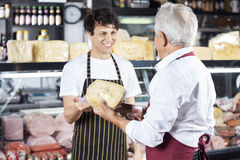 Collega di Receiving Cheese From del rappresentante in negozio Fotografia Stock Libera da Diritti