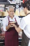 Collega di Receiving Cheese From del rappresentante in negozio di alimentari Immagini Stock Libere da Diritti