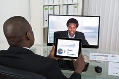 Collega di Video Chatting With dell'uomo d'affari sul computer Immagini Stock Libere da Diritti