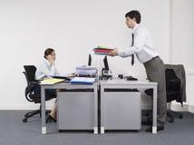 Collega femminile di Passing Folders To dell'uomo d'affari in ufficio immagine stock libera da diritti