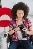 Collega femminile sulla sedia a rotelle facendo uso della macchina fotografica digitale immagini stock