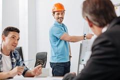 Collega's die aan de presentatie van een jonge bouwer luisteren stock fotografie