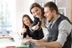 Collega's die aan een gemotiveerde arbeider op kantoor gelukwensen stock foto's