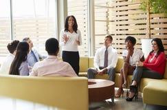Collega's die aan presentatie door een vrouwelijke manager luisteren stock foto's