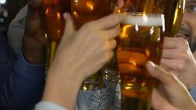 Collega's die bierglazen clinking, vierend bevordering na werkdag, carrière stock video