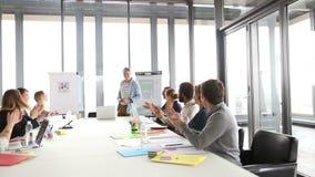Collega's die creatieve directeur toejuichen tijdens een vergadering stock videobeelden
