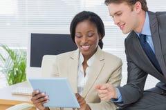 Collega's die digitale tablet in bureau gebruiken Royalty-vrije Stock Afbeelding