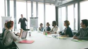 Collega's die directeur toejuichen tijdens een vergadering in conferentieruimte stock footage