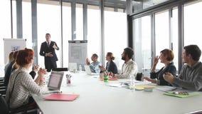 Collega's die directeur toejuichen tijdens een vergadering in conferentieruimte stock videobeelden