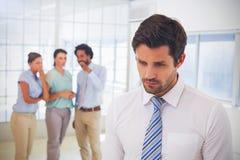 Collega's die met droevige zakenman in voorgrond roddelen stock illustratie